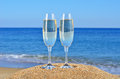 Glasses of champagne on the beach sand Stock Images