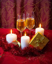 Glasses of champagne, candles, gold gift box and red tinsel Royalty Free Stock Photo