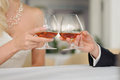 Glasses with cognac bride and groom clagning in cafe Royalty Free Stock Photos