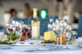 Glasses, forks, knives, napkins and decorative flower on a table served for dinner in cozy restaurant Royalty Free Stock Photo