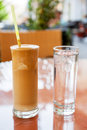 Glasses of frappe coffee and water served with a glass on cafe table crete greece Stock Photos