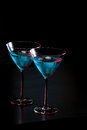 Glasses of fresh blue cocktail with ice on bar table red tint light and black background space for text Stock Image