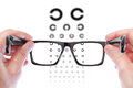 Glasses in the hands of men checking vision table golovin Royalty Free Stock Photography