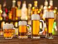 Glasses of light beer with bar on background served wooden desk Royalty Free Stock Images