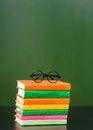 Glasses lying on the books near empty green chalkboard Royalty Free Stock Photo