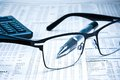 Glasses near calculator with pen on financial newspaper Royalty Free Stock Photo