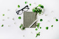 Glasses, old book, pen and branches with leaves and flowers on white background Royalty Free Stock Photo