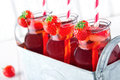 Glasses of red strawberry juice with frozen icecubes and striped straws in a metal vintage container Royalty Free Stock Images
