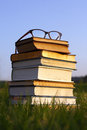 Glasses on stack of books outside a pair thick black women s eyeglasses sit top a thick old bibles and hymnals Stock Photography