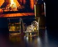 Glasses of whiskey with ice cubes near whiskey bottle in front of the fireplace Royalty Free Stock Photo