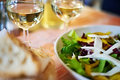 Glasses of white wine and salad on table cafe Royalty Free Stock Photo