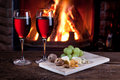 Glasses of wine cheese and nuts romantic still life near the fireplace Royalty Free Stock Images