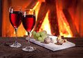 Glasses of wine cheese and nuts romantic still life near the fireplace Stock Image