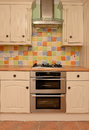 Glazed tile wall in modern kitchen with colorful ceramic and double stainless steel oven and gas stovetop Stock Image