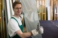 Glazier handling piece of glass in workshop Royalty Free Stock Photo