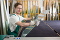 Glazier handling piece of glass in workshop worker s or warehouse Stock Photo
