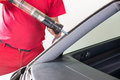 Glazier using application gun to apply adhesive for windscreen applying install new windshield or Stock Photos