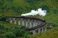 Glenfinnan viaduct with steamtrain the in scotland the jacobite steam train driving over it in green overgrown ambiance Stock Photography