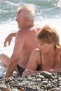 Gli accoppiamenti invecchiati si siedono su Pebble Beach Fotografia Stock