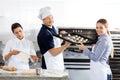 Glimlachende chef kok passing baking sheet aan collega binnen Royalty-vrije Stock Fotografie