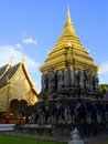 Glimmering pagoda a golden bordered by elephant statues reaches for the sky in the background a temple building houses a sacred Stock Photography