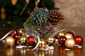 Glitter covered pine cones and christmas bulbs a crystal bowl of decorations sitting on a wooden table top in front of a tree Stock Photography