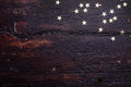 Glitter golden stars on grunge wood background. Royalty Free Stock Photo
