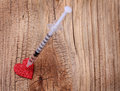 Glitter red heart and syringe with drug over wooden background addiction concept Royalty Free Stock Photo