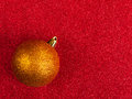 Glittery gold baublered on glittery background Royalty Free Stock Images