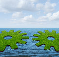 Global business connections with two green grass islands floating on the ocean shaped as a gear or cog coming together to create Royalty Free Stock Image