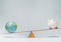 Global business world globe and piggy bank balancing on a seesaw Stock Photos