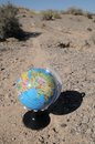 Globe in the desert on a road a mountain Royalty Free Stock Image