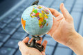 Globe in hand against the background of the keyboard Royalty Free Stock Photo