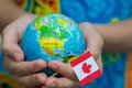 Globe in hand with the Canada flag