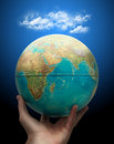 Globe in hand with clouds Royalty Free Stock Image