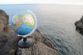 A globe on a rock near the atlantic ocean Royalty Free Stock Photos