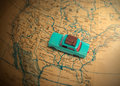 Globetrotting car holiday vacation toy with luggage on a vintage globe map of the united states with a shallow depth of field Stock Photos