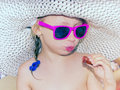 Glomour girl little glamour in pink glasses eating sausage on the beach outdoor Stock Photo