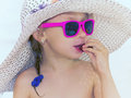 Glomour girl little glamour in pink glasses eating sausage on the beach outdoor Stock Photos