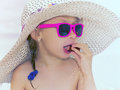 Glomour girl little glamour in pink glasses eating sausage on the beach outdoor Stock Images