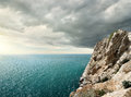 Gloomy clouds over the sea and rocky mountain Stock Photo
