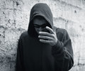 Gloomy man in a hood on the street Stock Photography
