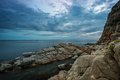 Gloomy sky over rocky shore Stock Photo