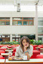 Gloomy student in the cafeteria with food tray female sitting Stock Photography
