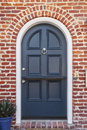 Glossy blue door to classic brownstone home a lacquered front a family is featured under brick arch with knocker and a plant in Royalty Free Stock Photo