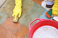 Gloved hand cleaning of dirty filthy floor in yellow glove with brush indoors Stock Image