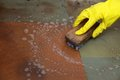 Gloved hand cleaning of dirty filthy floor in yellow glove with brush indoors Stock Photos