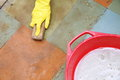Gloved hand cleaning of dirty filthy floor in yellow glove with brush indoors Royalty Free Stock Images