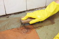 Gloved hand cleaning of dirty filthy floor in yellow glove with brush indoors Royalty Free Stock Image