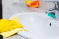 Gloved hand cleaning sink edge Royalty Free Stock Photo